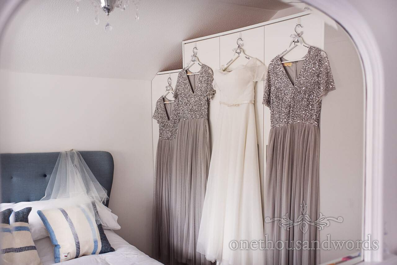 White wedding dress hangs with silver bridesmaids dresses in mirror