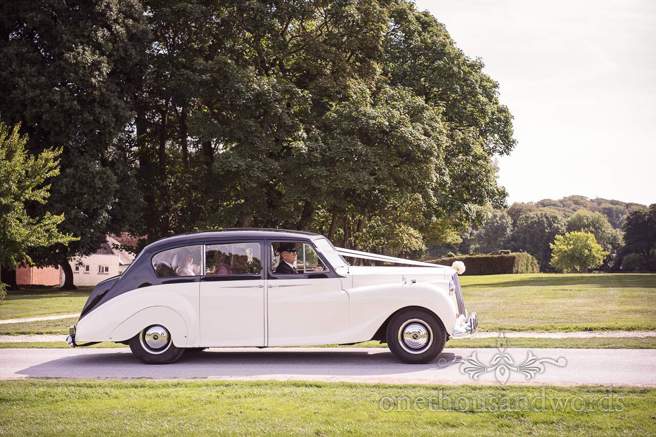 Bridal party arrive in classic wedding car for woodland Lulworth Castle wedding