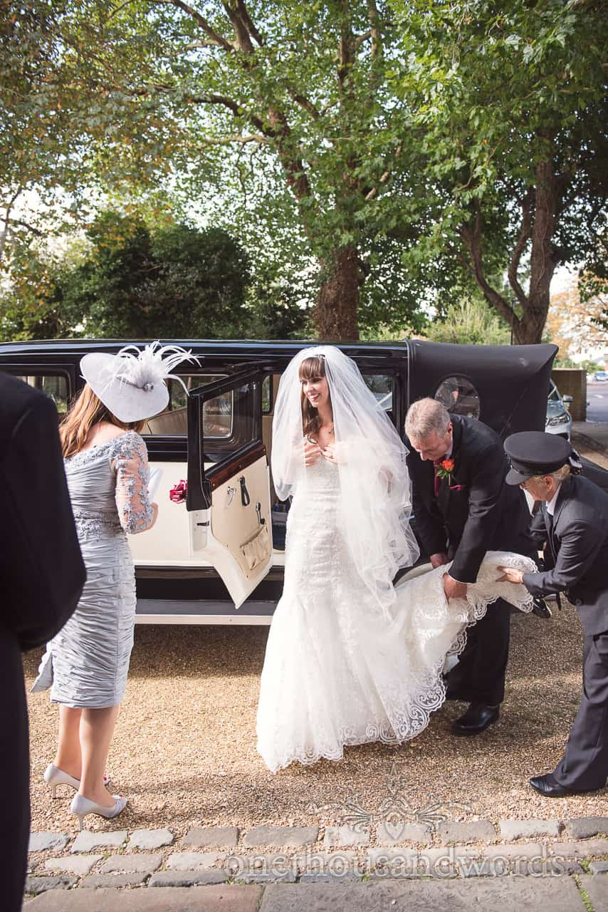 Bride is helped out of classical wedding car by father and chauffeur