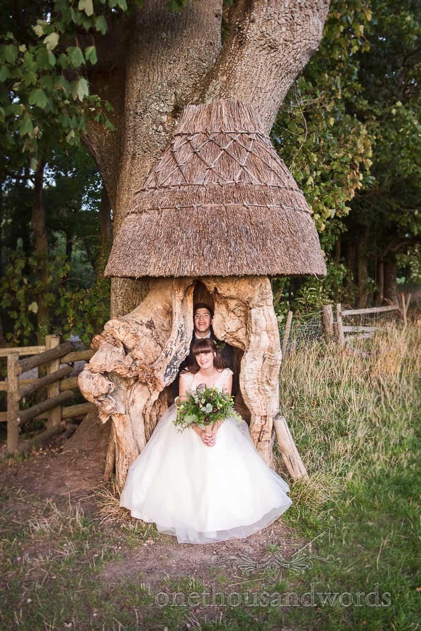 Bride adn groom inside wooden tree stump at Woodland Lulworth Castle Wedding