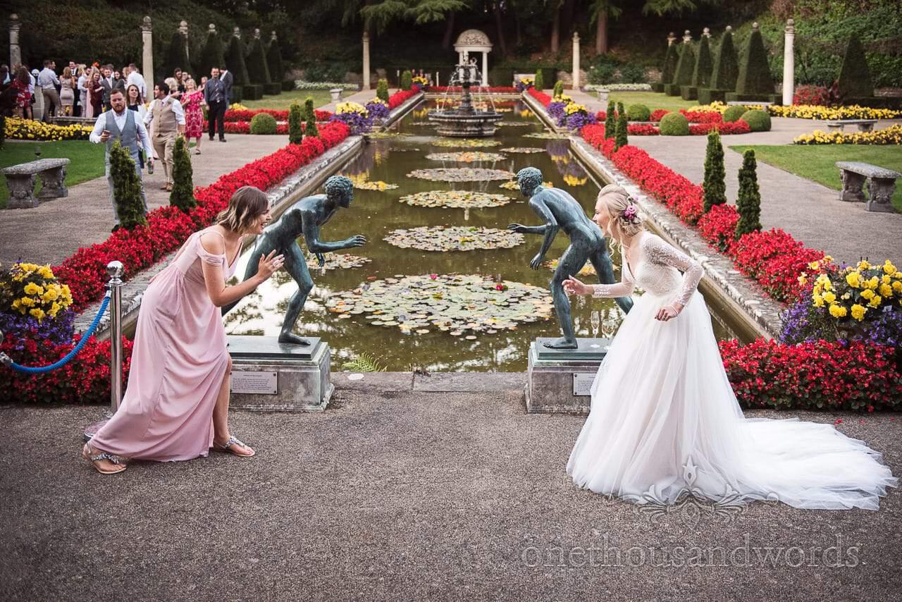 Bride and bridesmaid pose like statues in garden at Italian Villa wedding