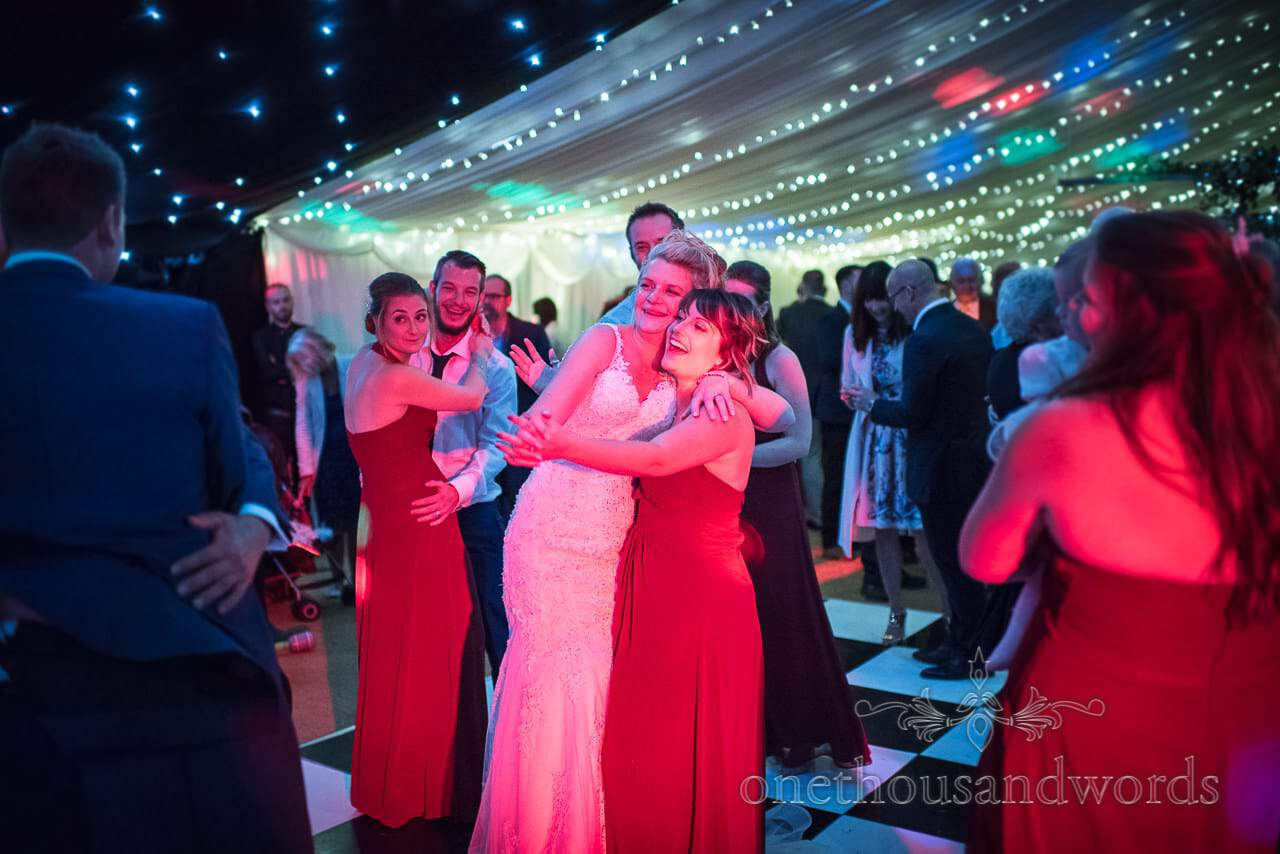Bride and bridesmaids on the dance floor at Farm Marquee Wedding