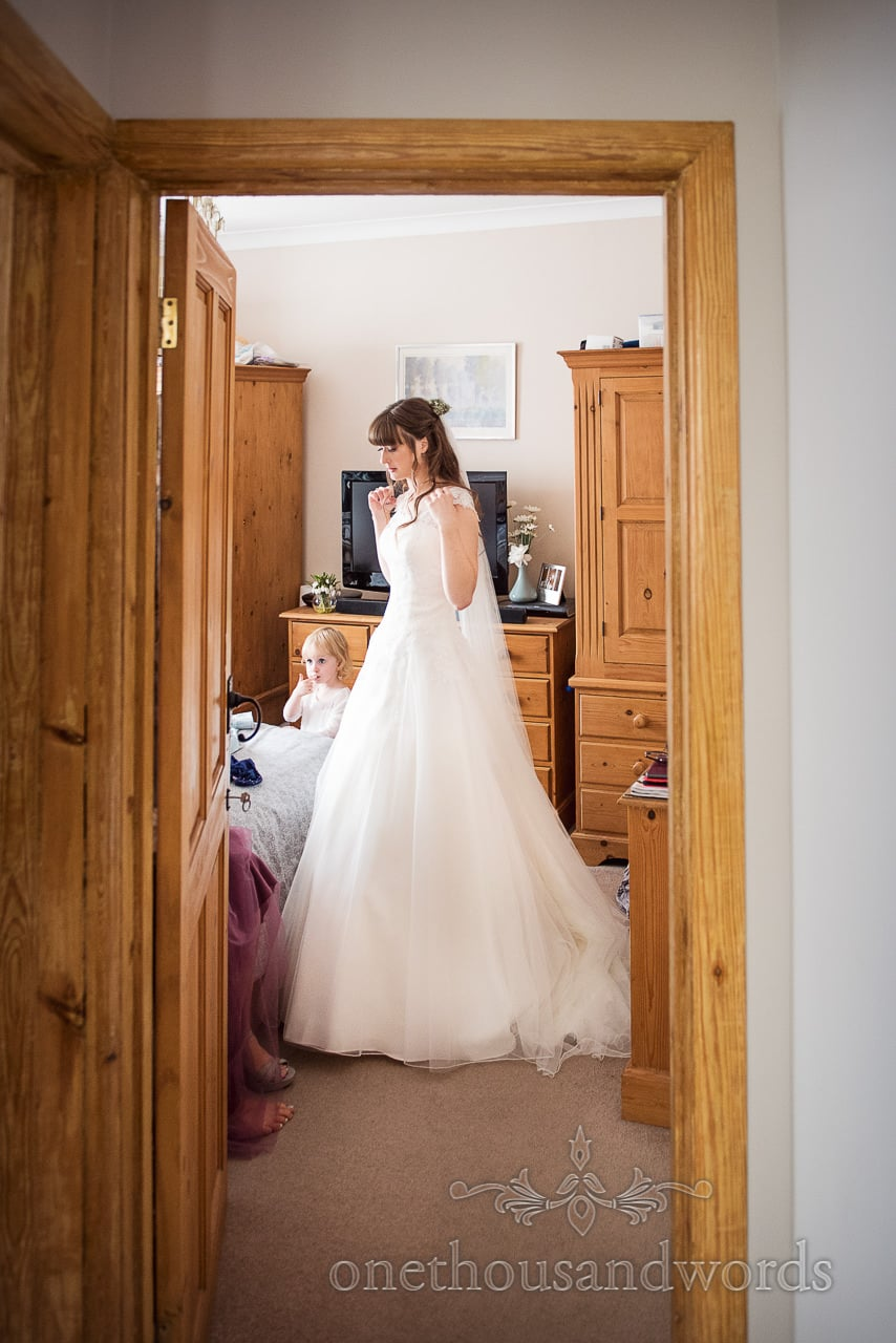 Bride and flower girl in doorway from morning of woodland Lulworth Castle wedding