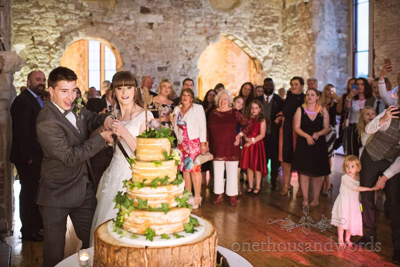 Bride and groom cut wedding cake with sword at Lulworth Castle Wedding