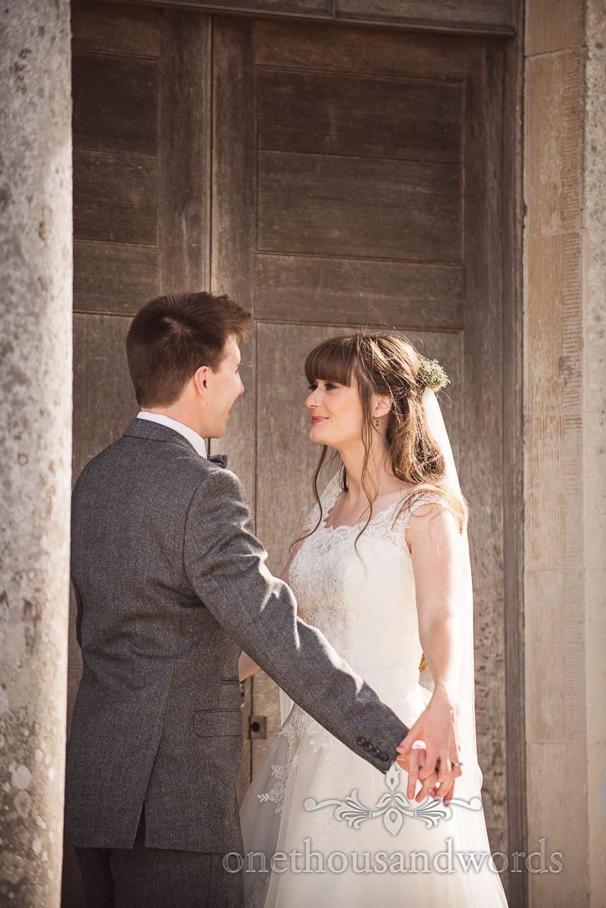 Bride and groom in chapel doorway from woodland Lulworth Castle wedding