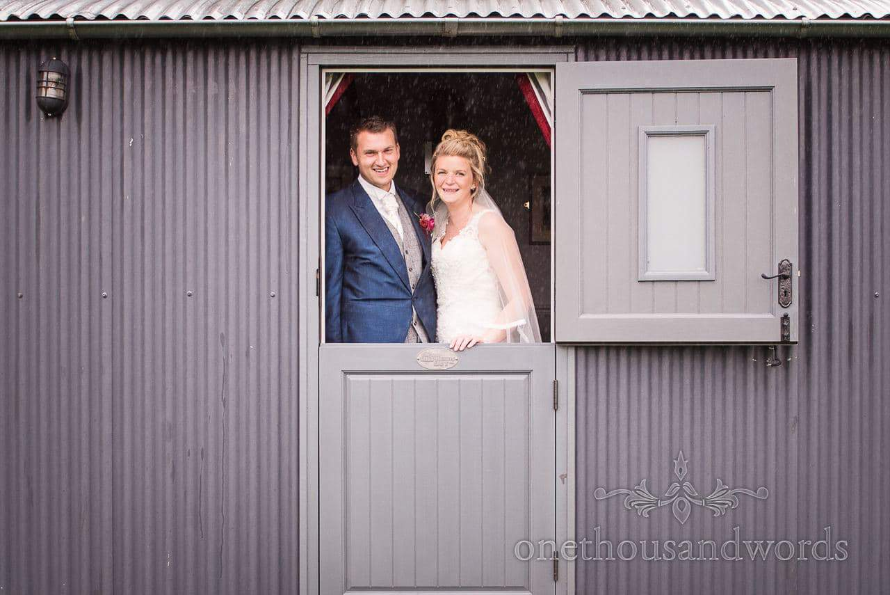 Bride and groom in door way of shepherds hut during marquee reception