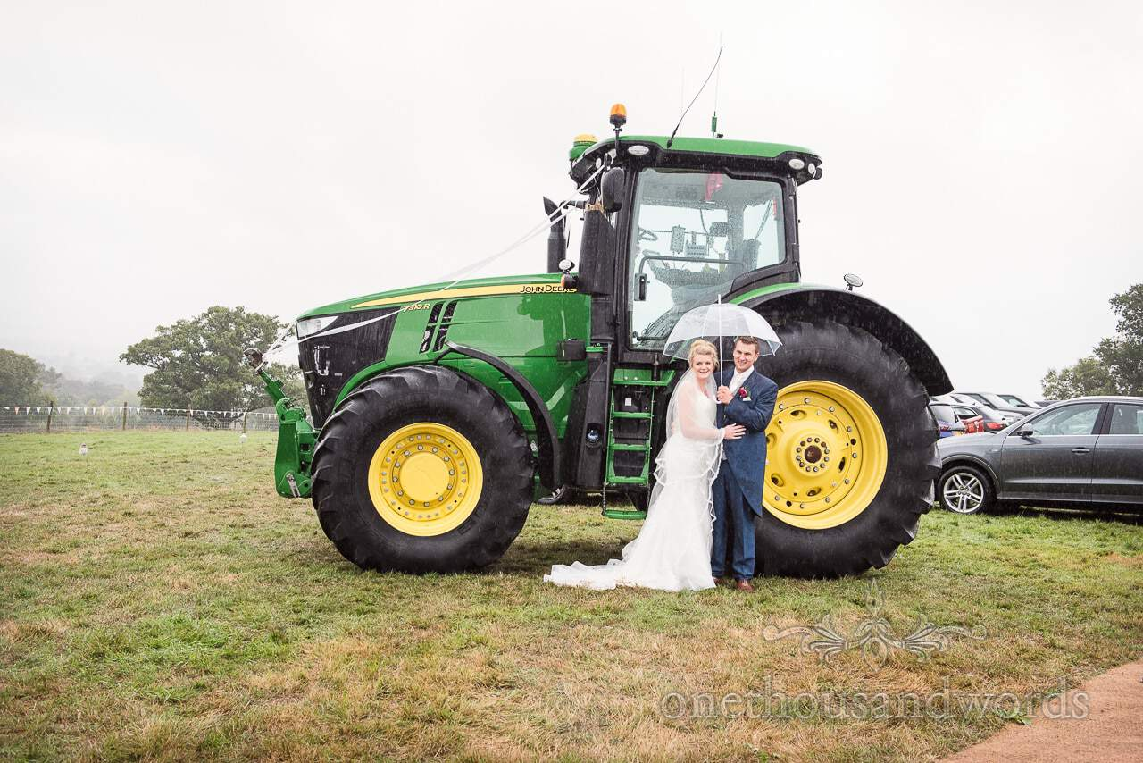 Bride and groom pose under umbrella in front of grooms tractor