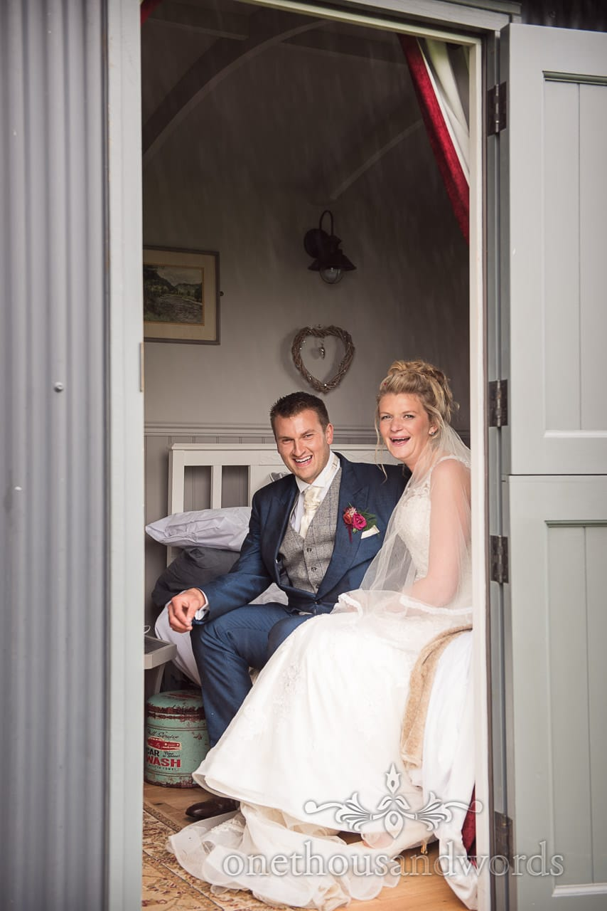 Bride and groom shelter from rain inside shepherds hut during marquee reception