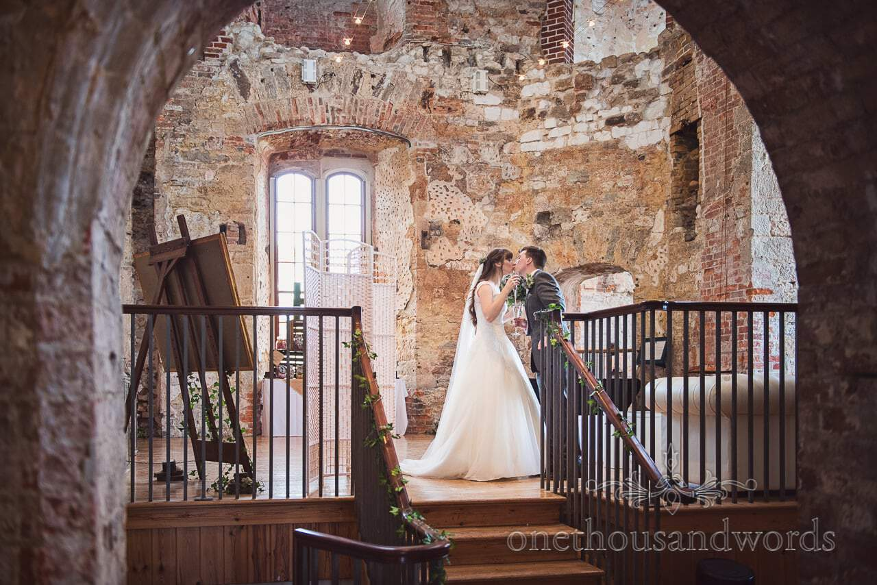Bride and groom steal a kiss when nobody's looking at woodland Lulworth Castle wedding