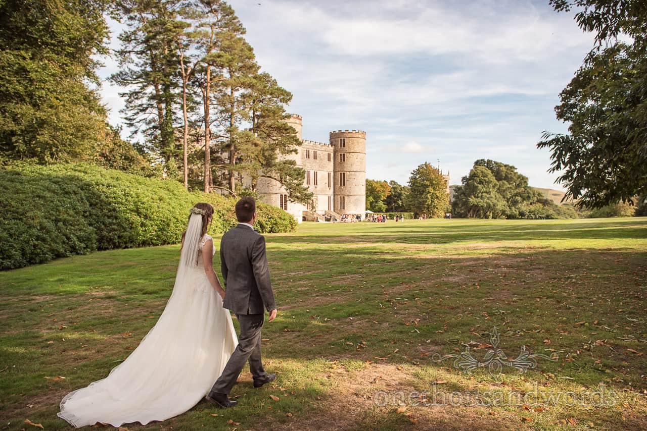 Bride and groom walk back towards castle at woodland Lulworth Castle wedding