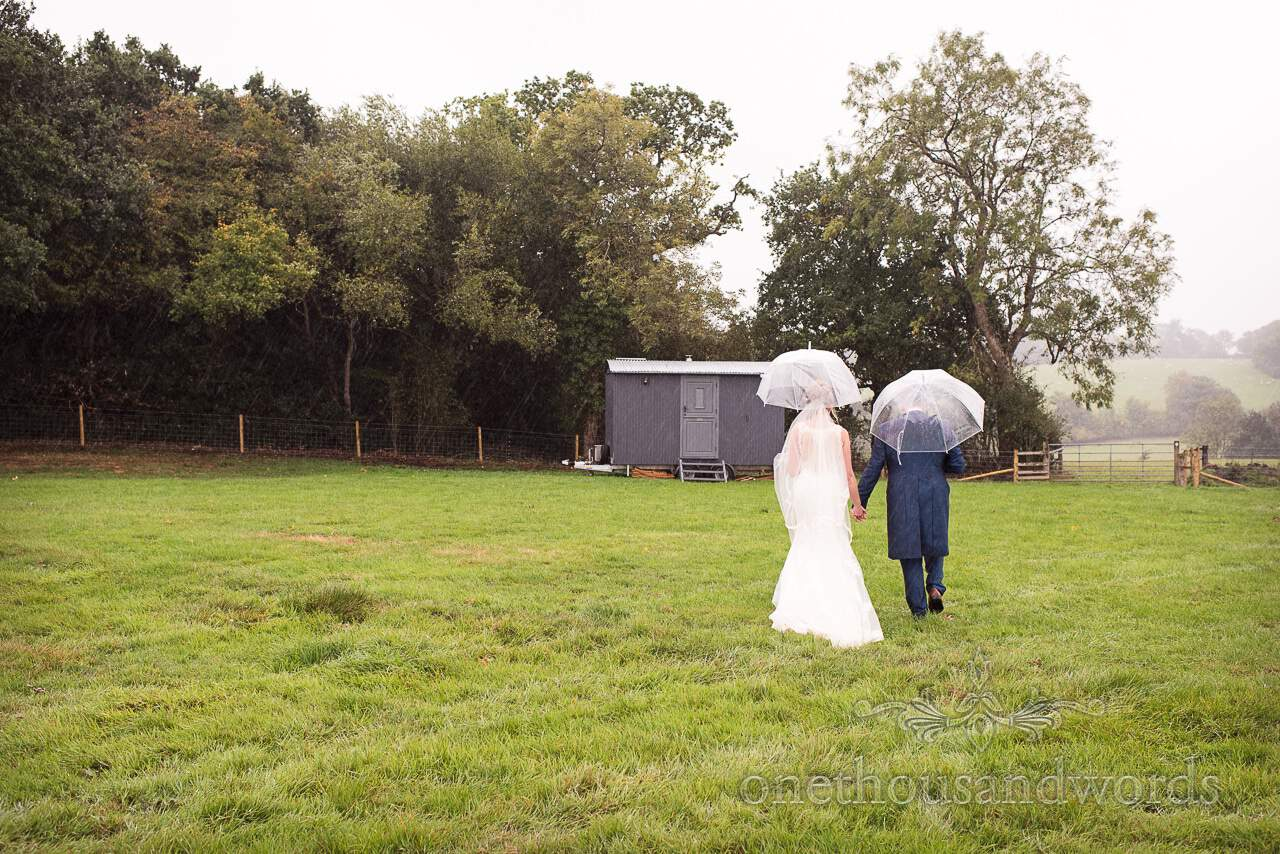 Bride and groom walking towards shepherds hut during marquee reception