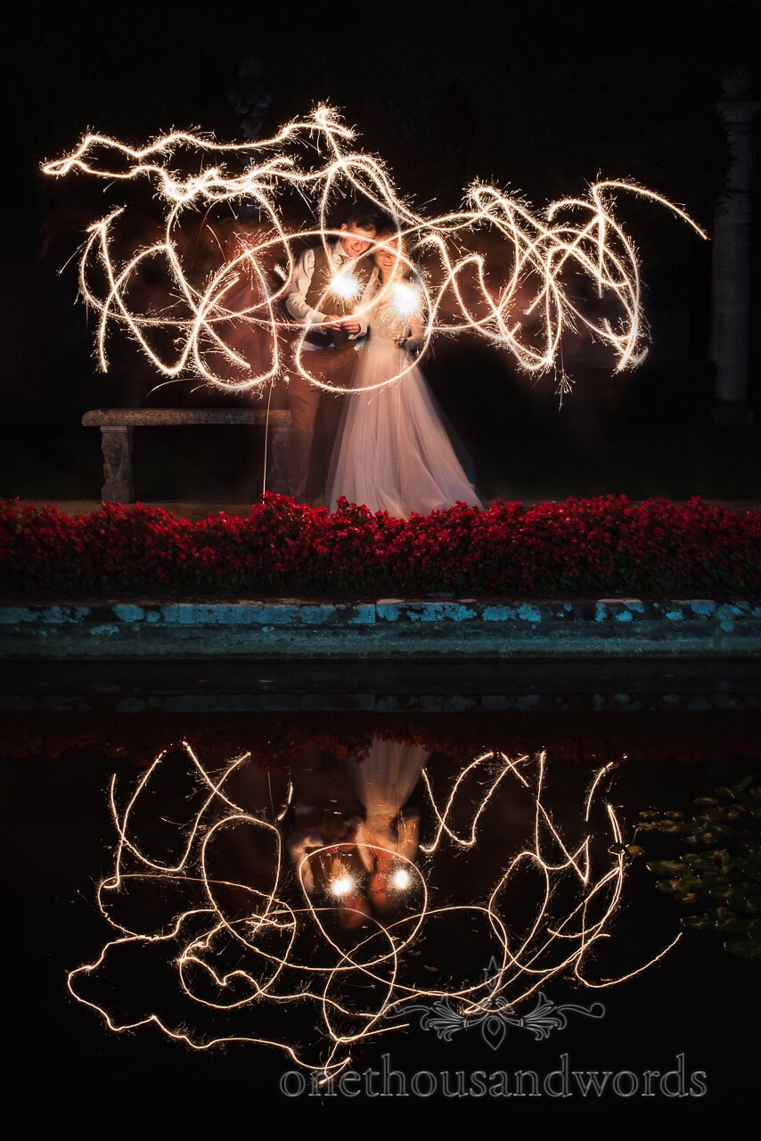 Bride and groom with sparkler trails reflected in lake at The Italian Villa gardens