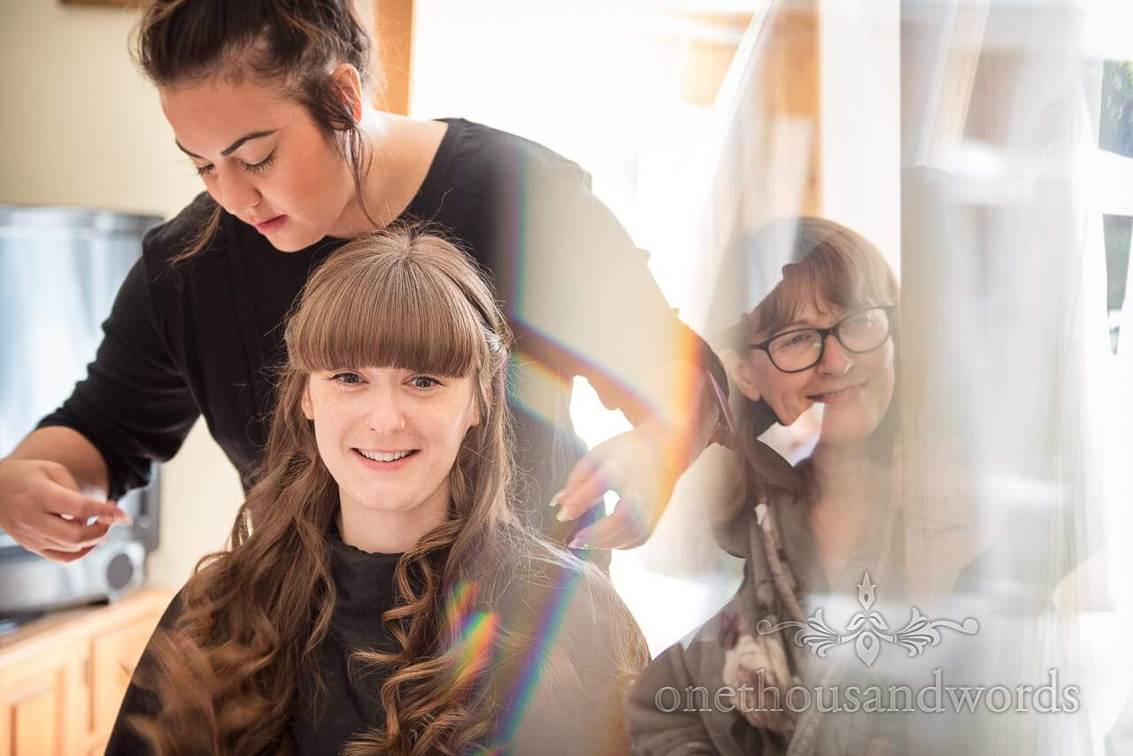 Bride and mother during hair styling on morning of woodland Lulworth castle wedding