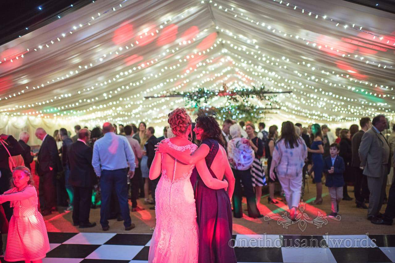 Bride and mother in law share a moment in wedding marquee