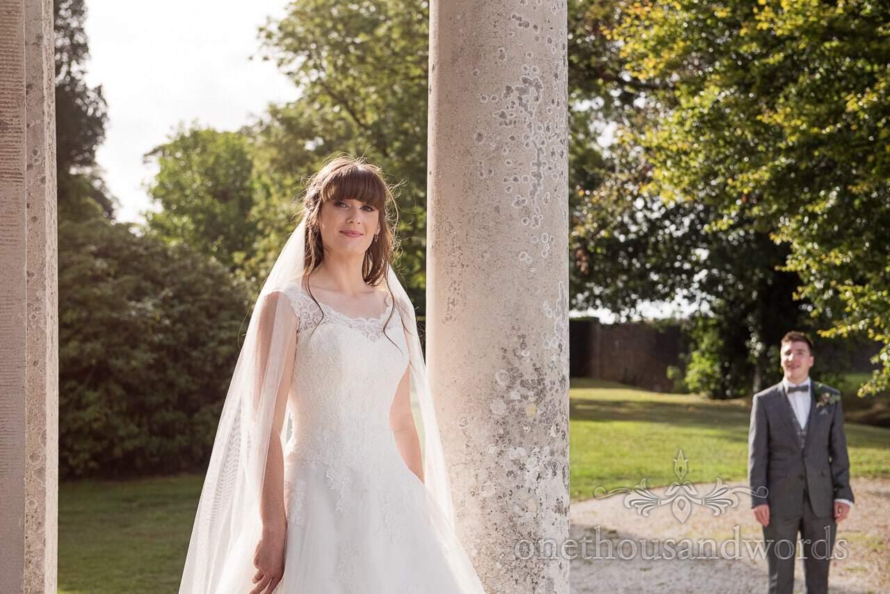 Bride as groom looks on at woodland Lulworth Castle wedding