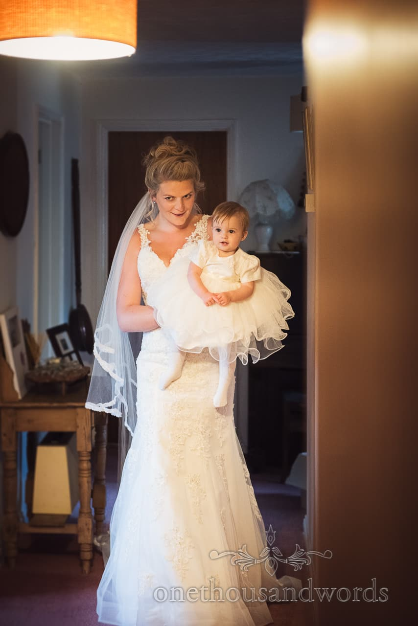 Bride carries infant flower girl during morning of farming wedding