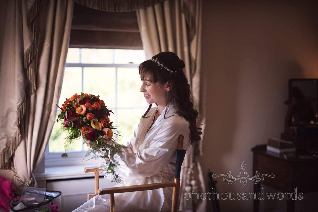 Bride examines red and orange bridal bouquet at Hethfelton House