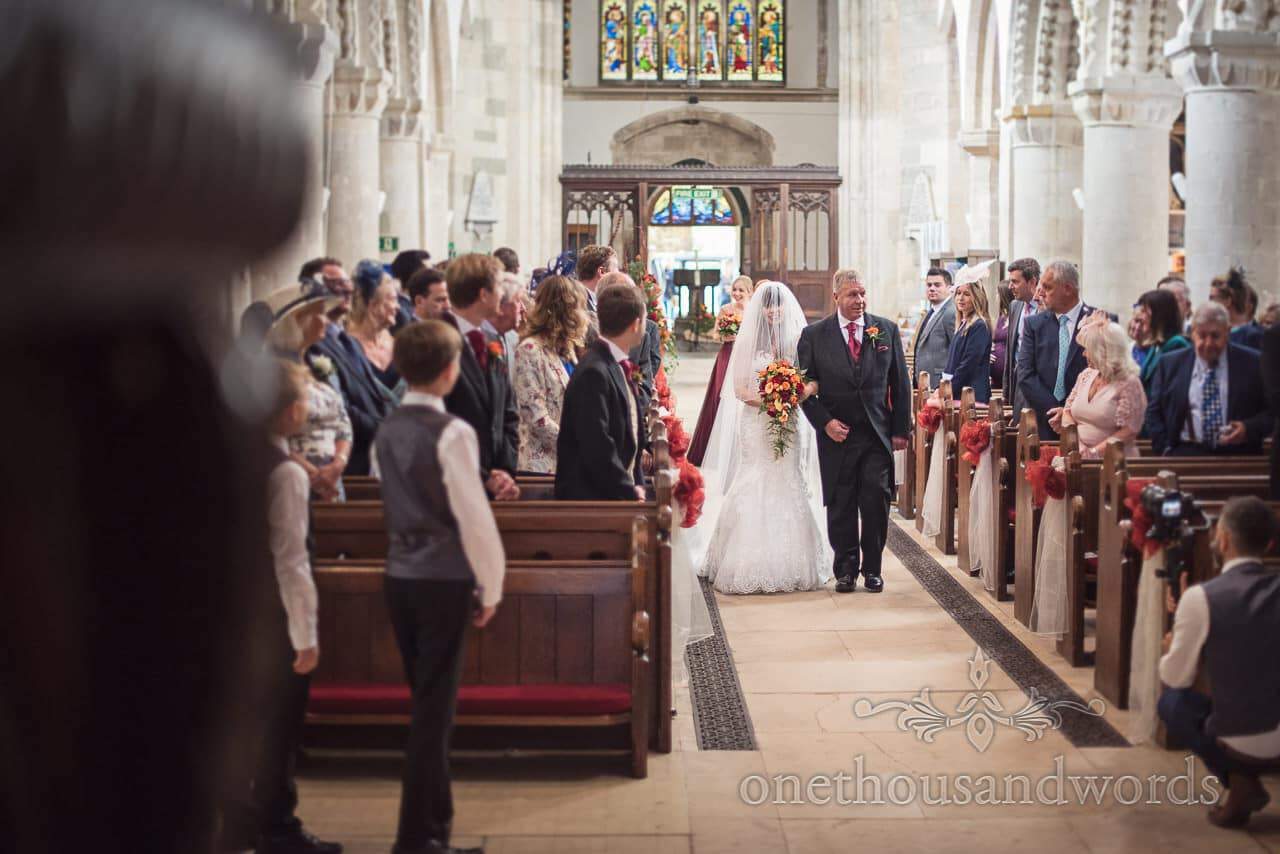Bride and father walk down the aisle at Wimborne Minster wedding