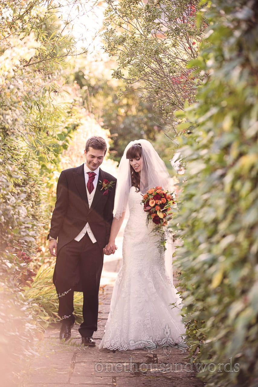 Bride and groom walk through Hethfelton House Wedding gardens