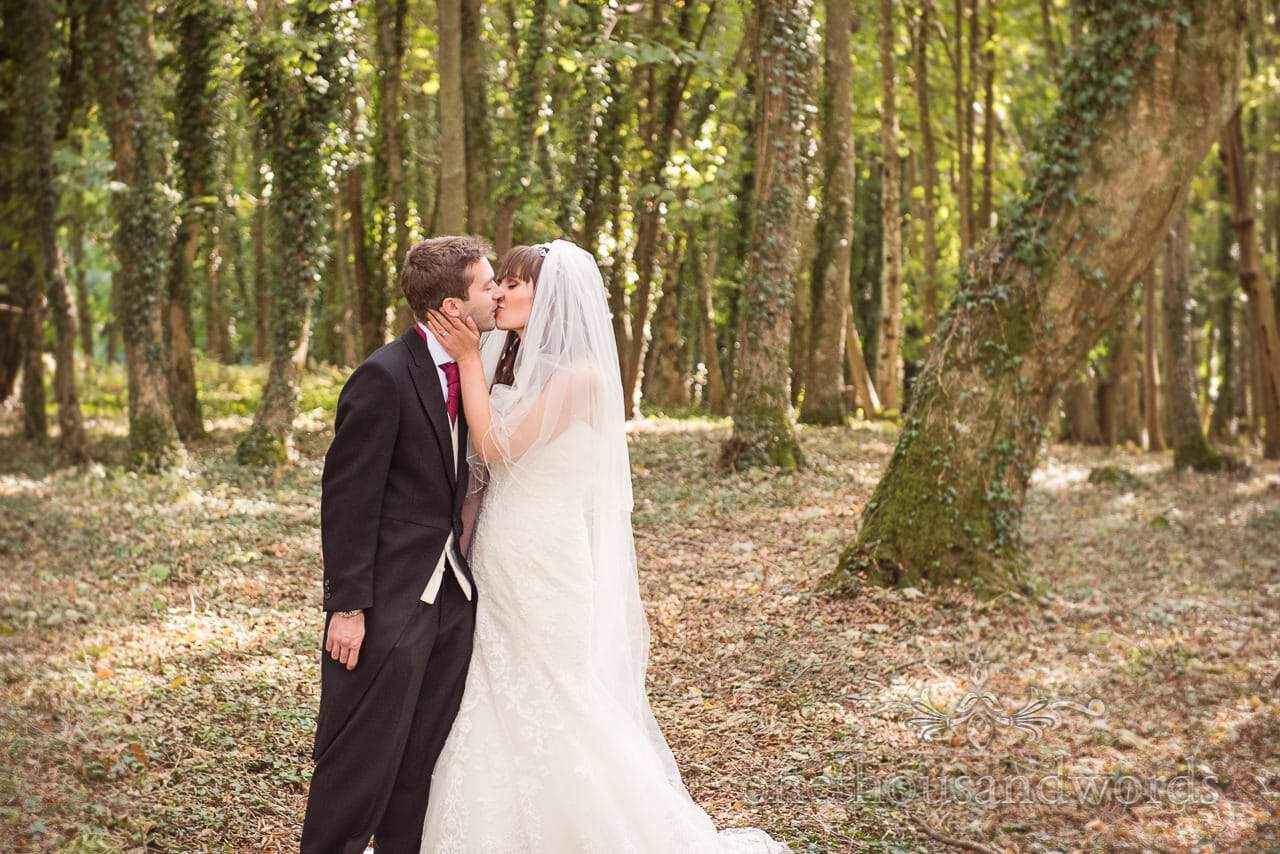 Bride and groom kiss in Hethfelton House woodland on wedding day