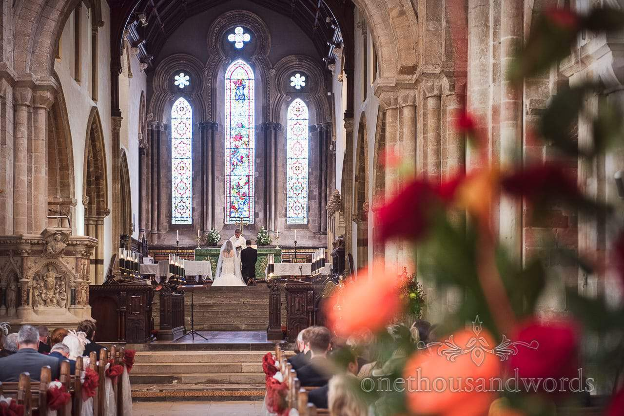 Bride and groom kneel before the altar at Wimborne Minster wedding