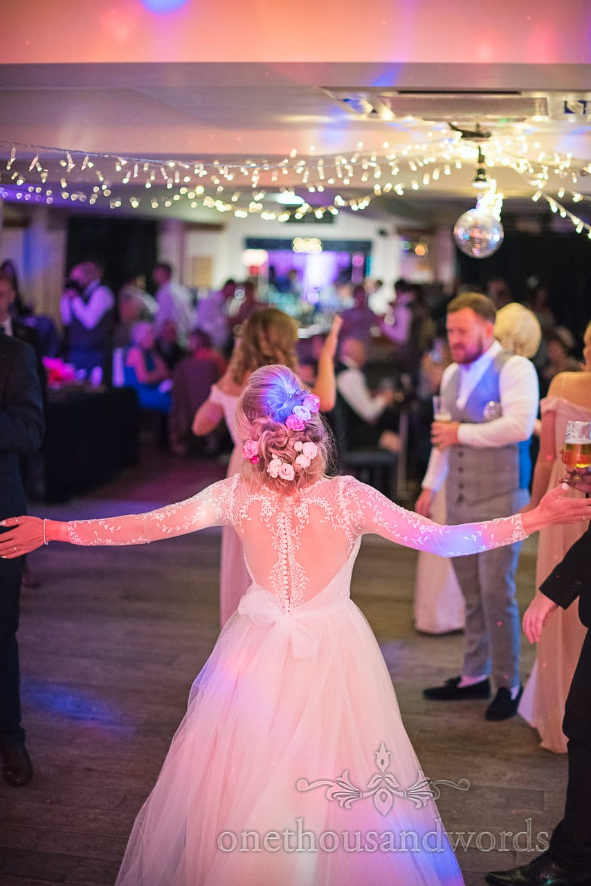Bride in detailed wedding dress with arms out on wedding dance floor at Italian Villa