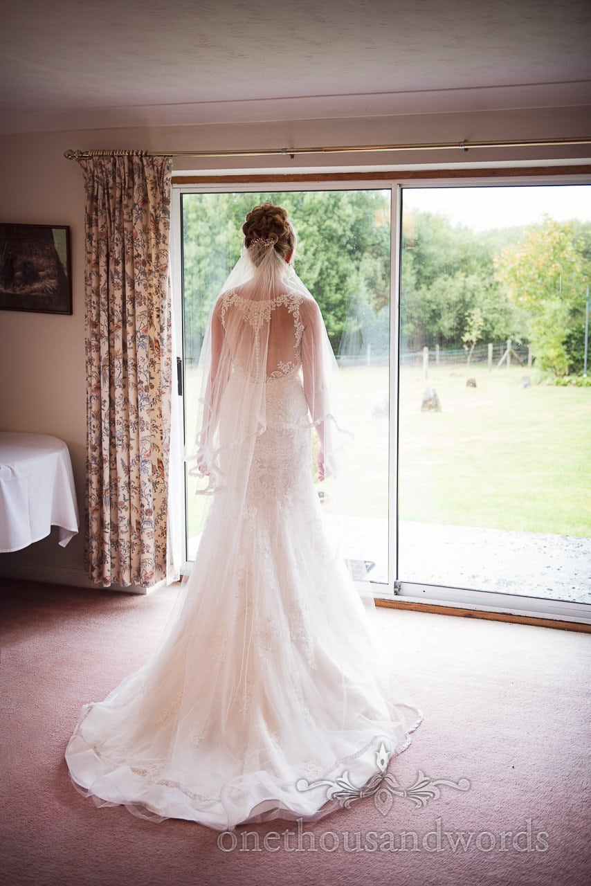 Bride in dress and veil looks out window on wedding morning