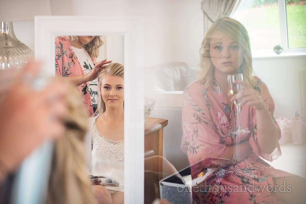 Bride in mirror has hair styled while bridesmaid looks on before Italian Villa wedding
