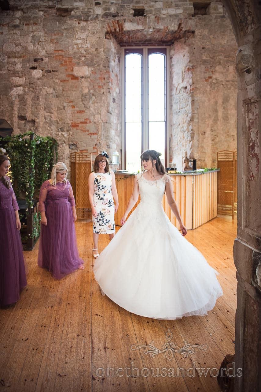 Bride in white wedding dress twirls in bar area at Lulworth Castle Wedding venue