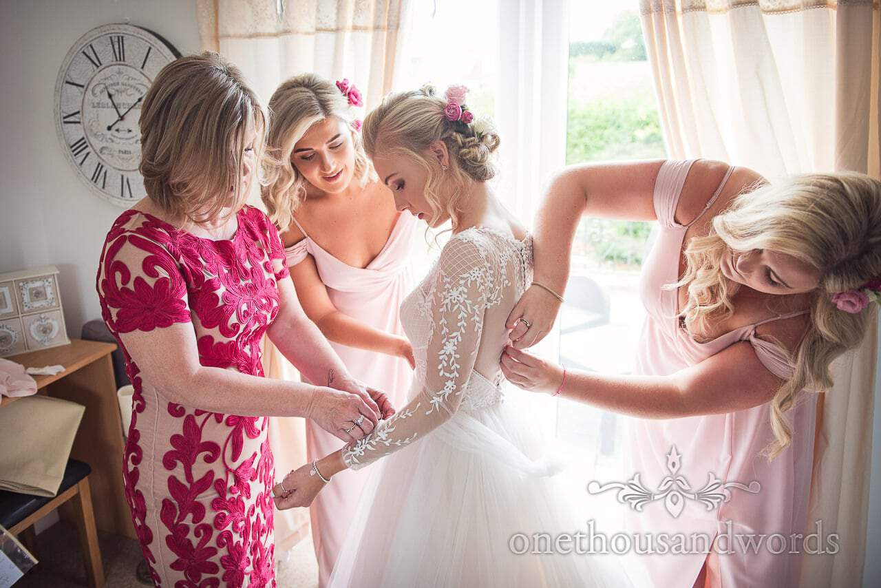 Bride is helped into dress by mother and bridesmaids before Italian Villa wedding