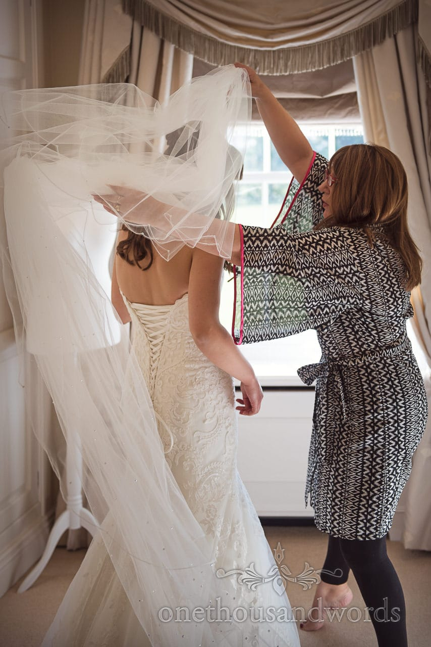 Bride has large veil put on in Hethfelton House Wedding venue