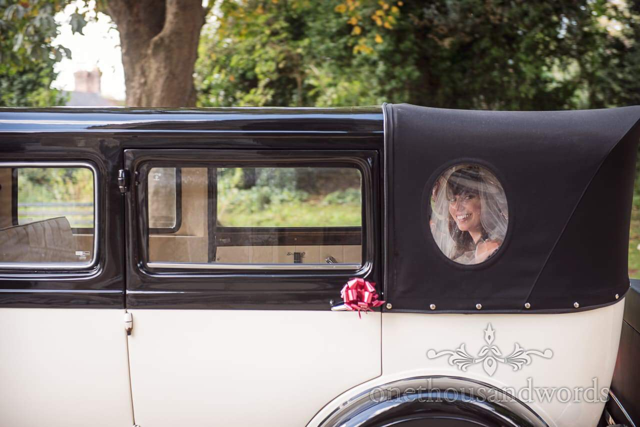 Bride looks out of porthole window in rear of classical wedding car