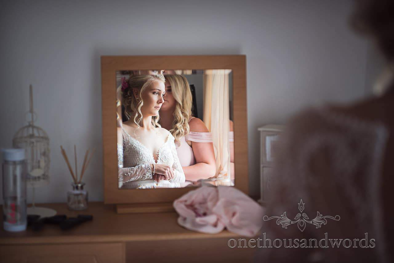 Bride looks thoughtful in mirror on morning of Italian Villa wedding