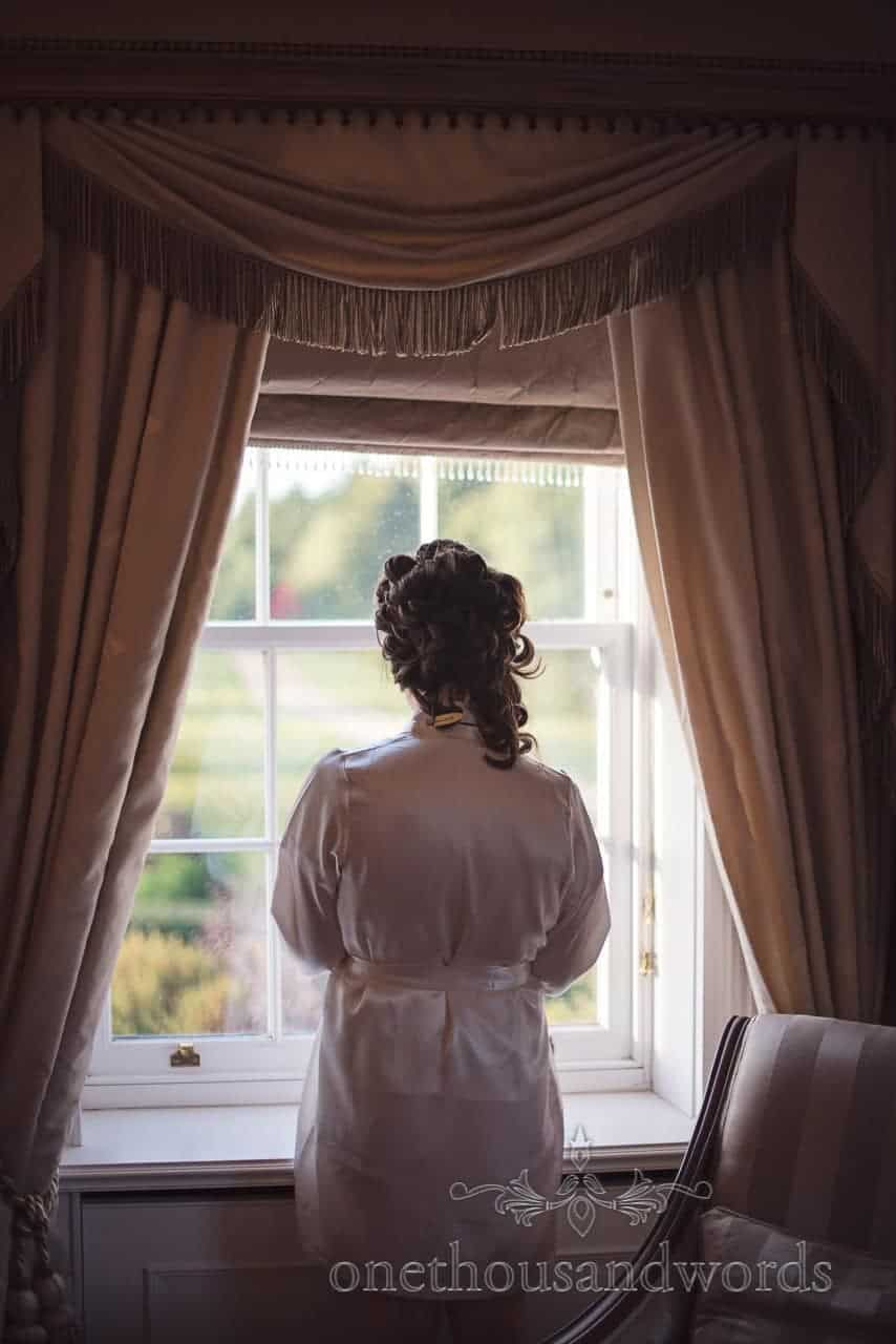 Bride looks out of window at Hethfelton House Wedding venue