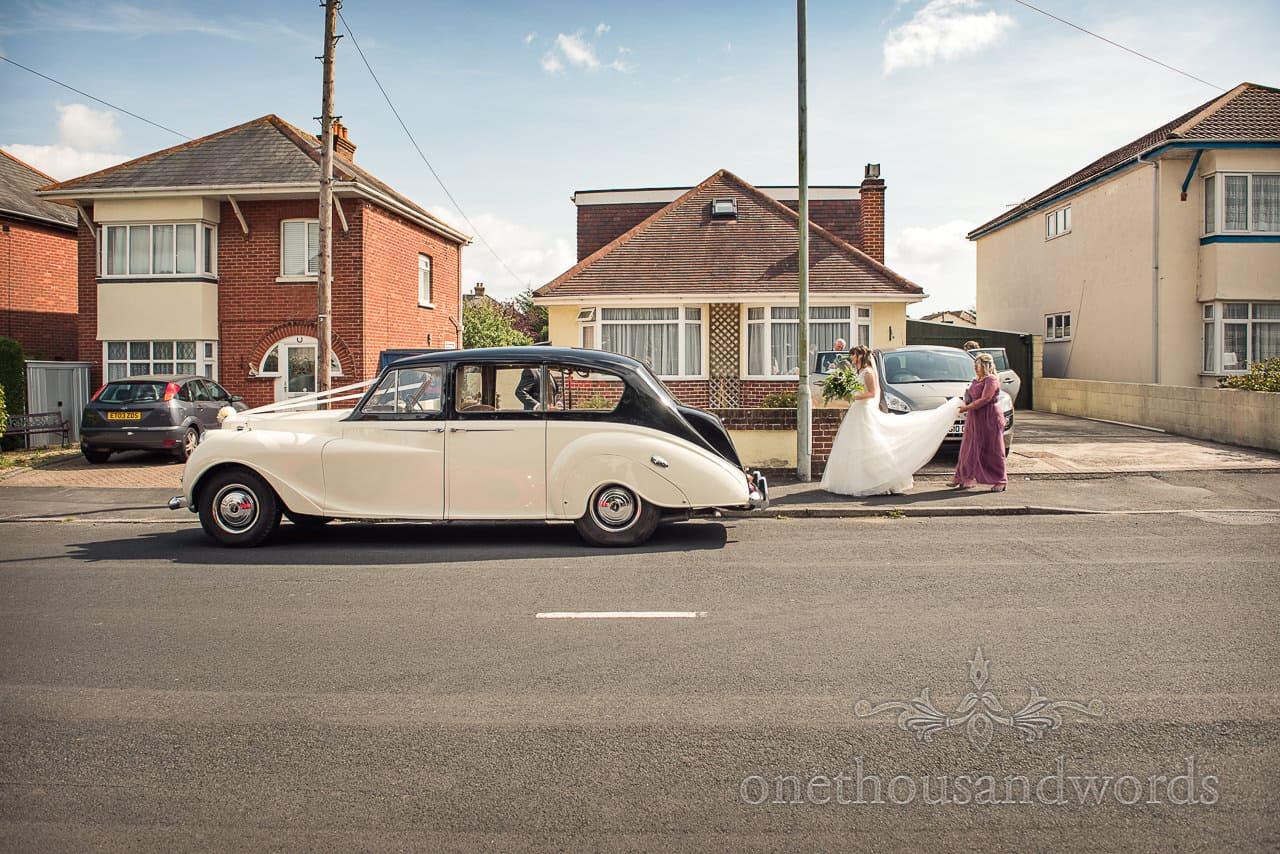 Bride makes here way to wedding car before woodland Lulworth Castle wedding