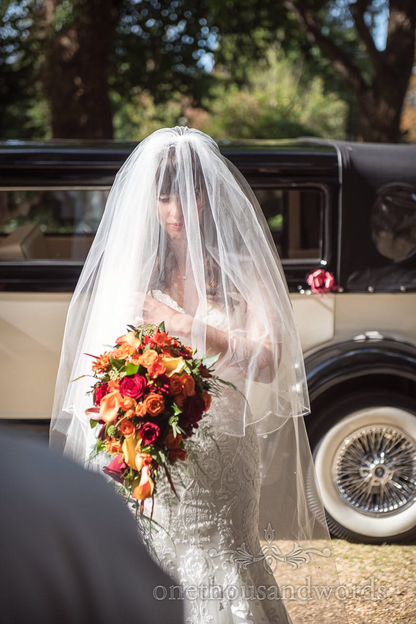 Bride with veil over face walks from classical wedding car in the sun
