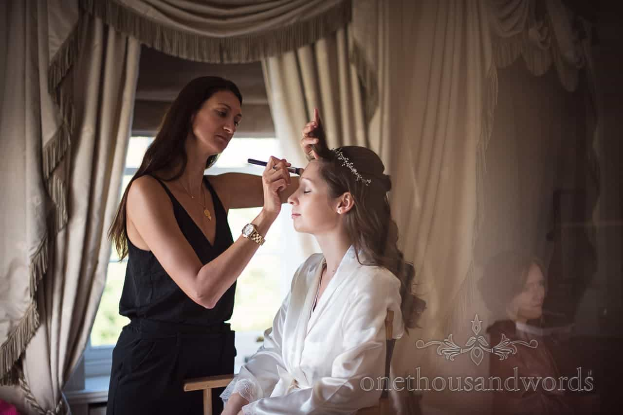 Bride has wedding make up styled watched by bridesmaid on morning