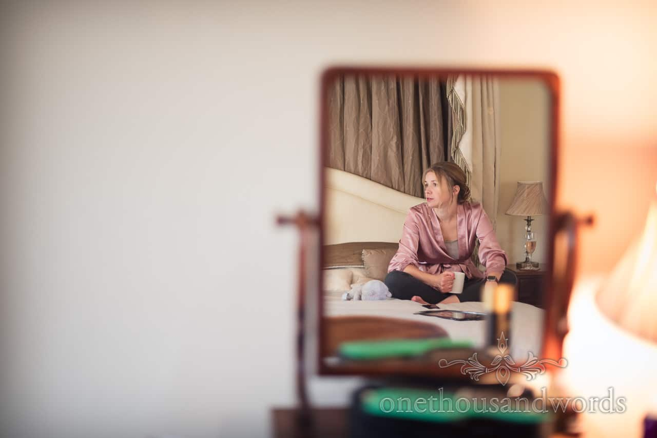 Bridesmaid with cup of tea in mirror during morning bridal preparations