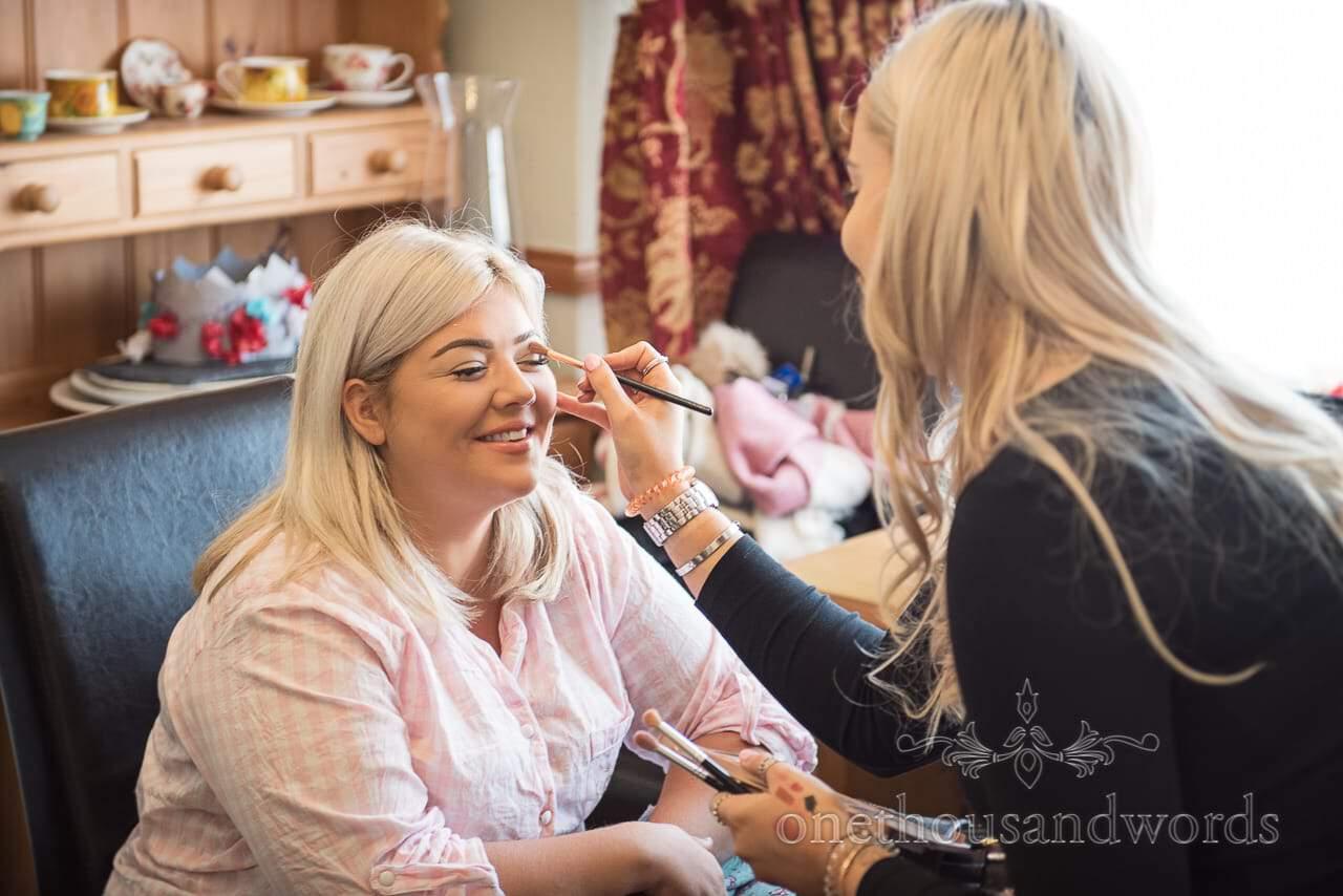 Bridesmaid has make up styled on morning of woodland Lulworth Castle wedding