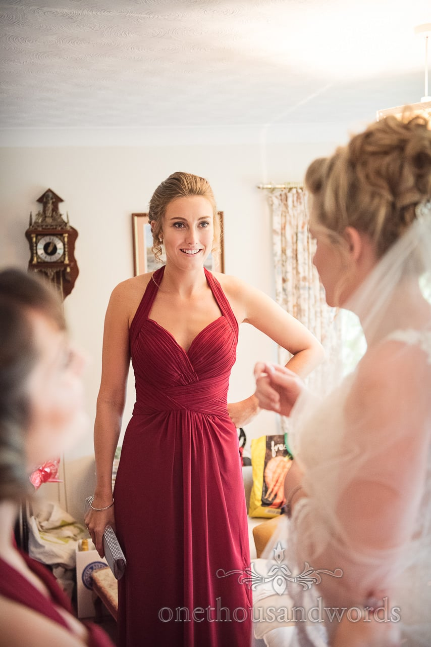 Bridesmaid in deep red dress during wedding morning