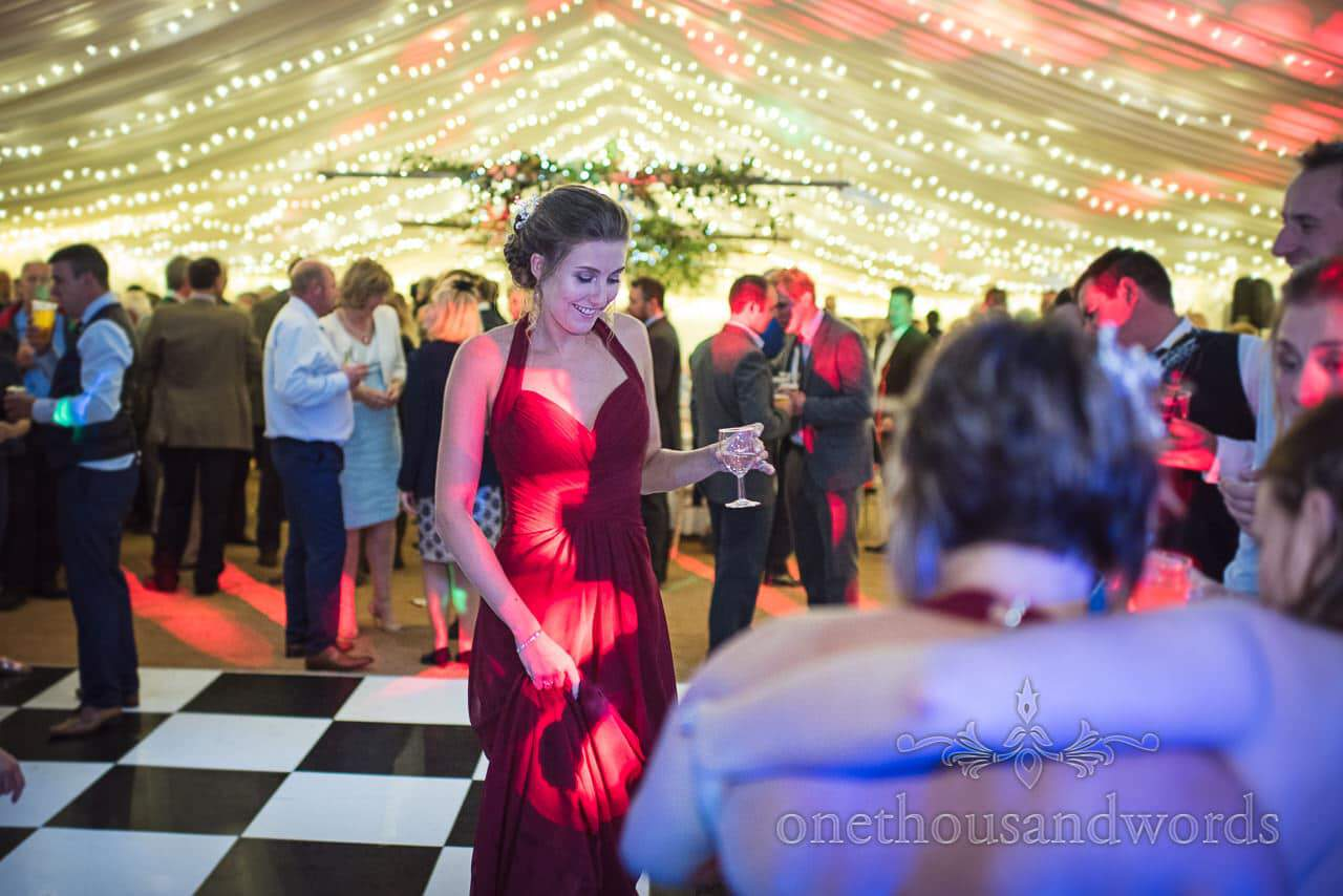 Bridesmaid in red dress dances on marquee wedding dance floor with coloured lights