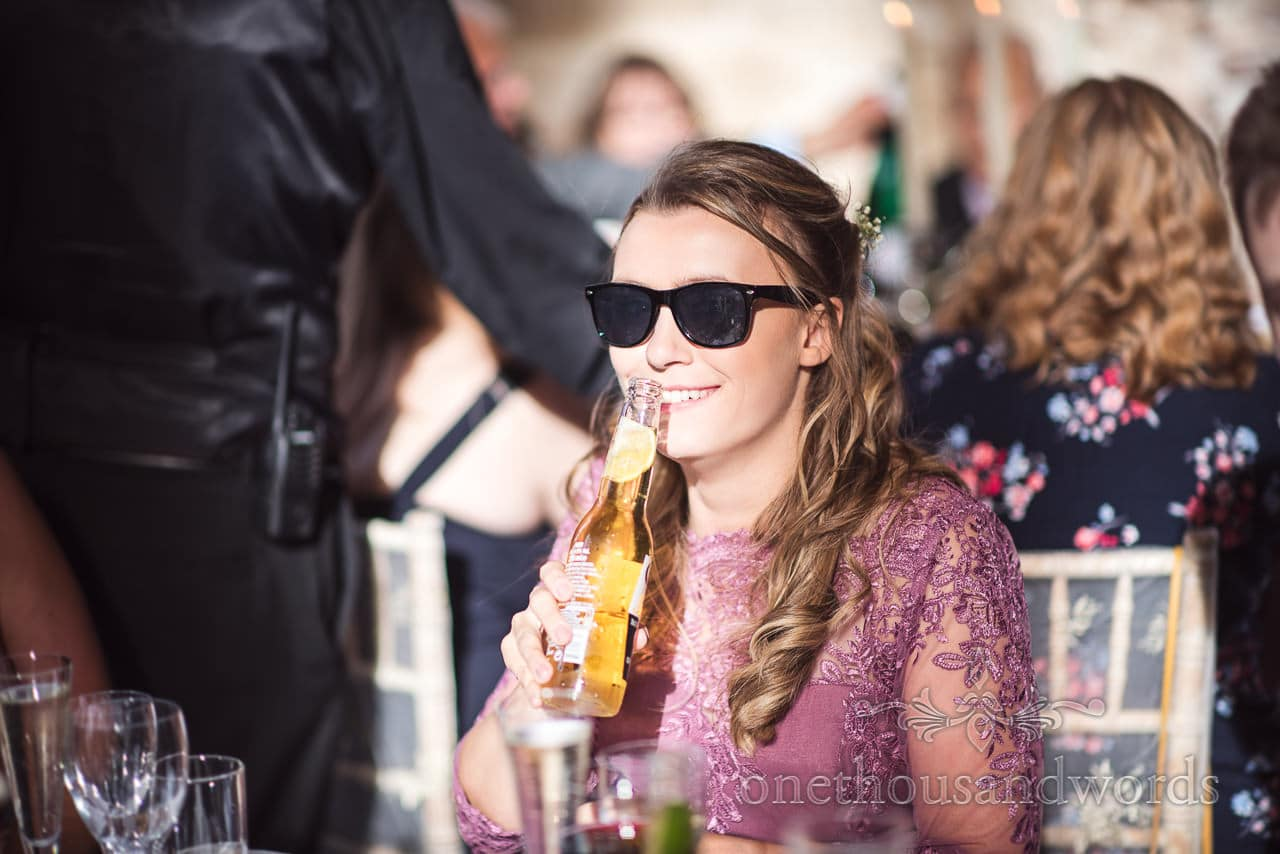 Bridesmaid in sunglasses with beer at woodland Lulworth Castle wedding