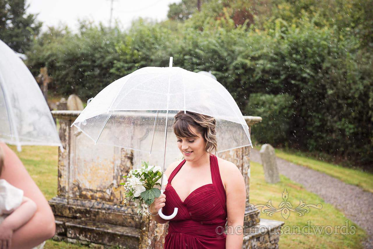 Bridesmaid on way to church with umbrella farm marquee wedding photos