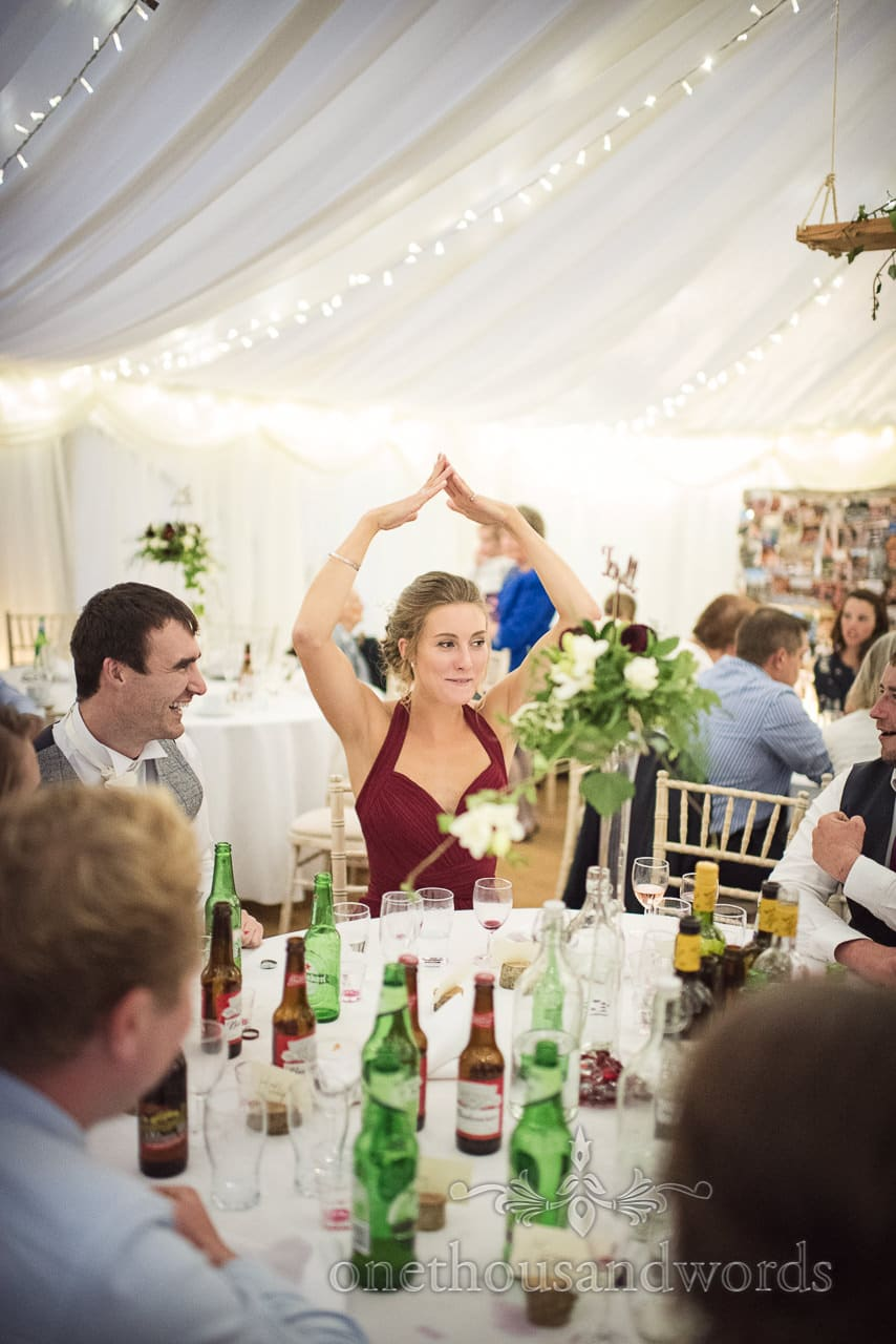 Bridesmaid plays drinking game with arms above head at wedding