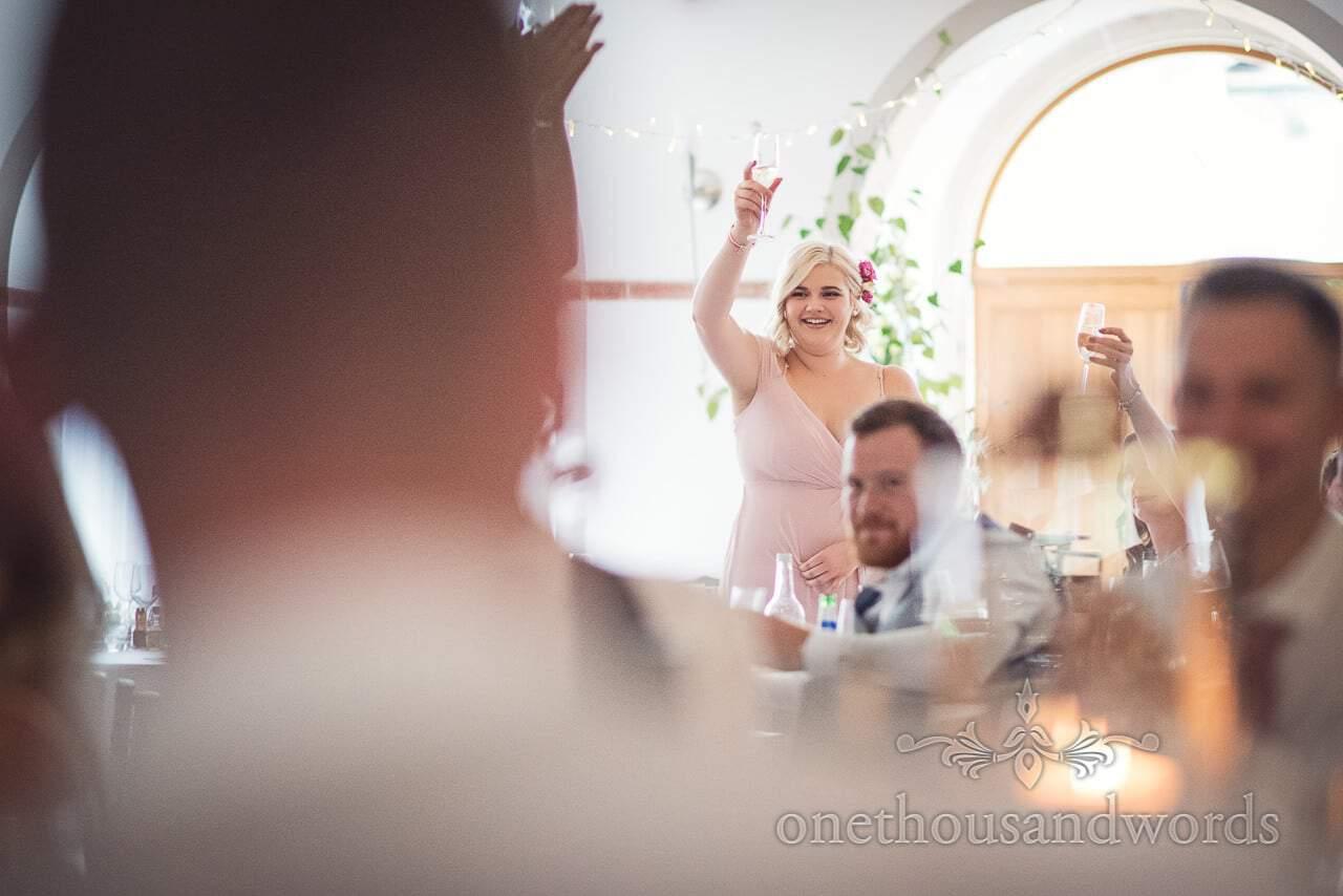 Bridesmaid raises glass to toast during speeches at Italian Villa wedding