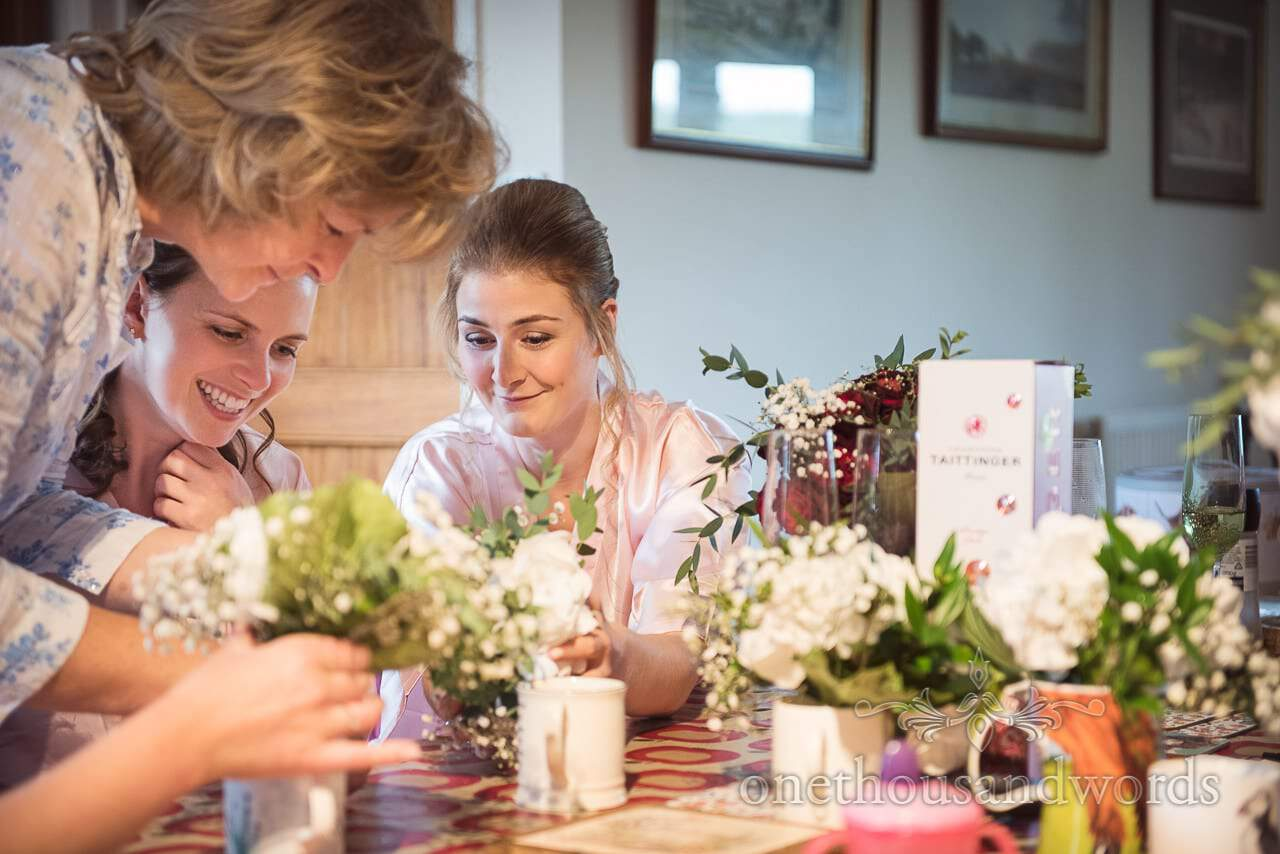 Bridesmaids and mother of the bride make bouquets for farm marquee wedding