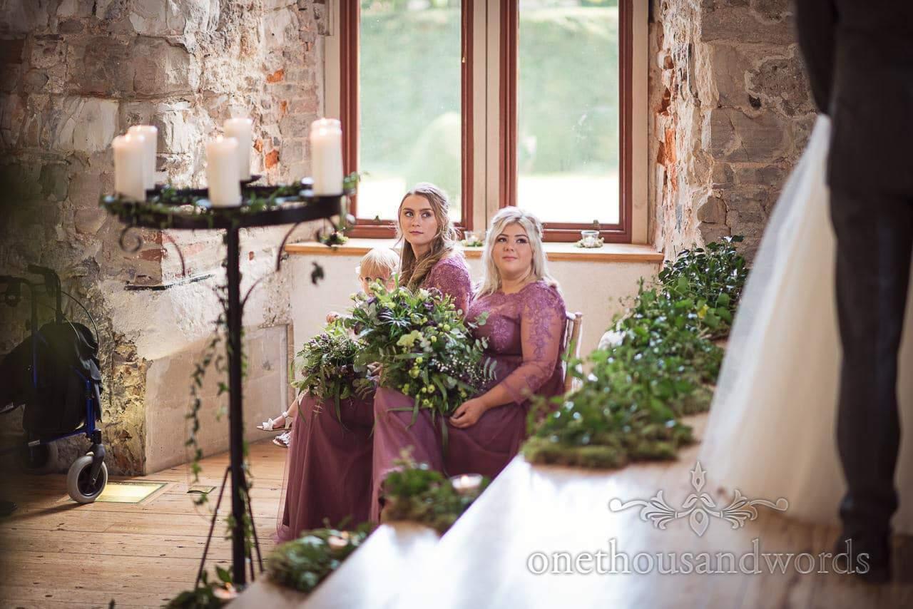 Bridesmaids during ceremony at woodland Lulworth Castle wedding