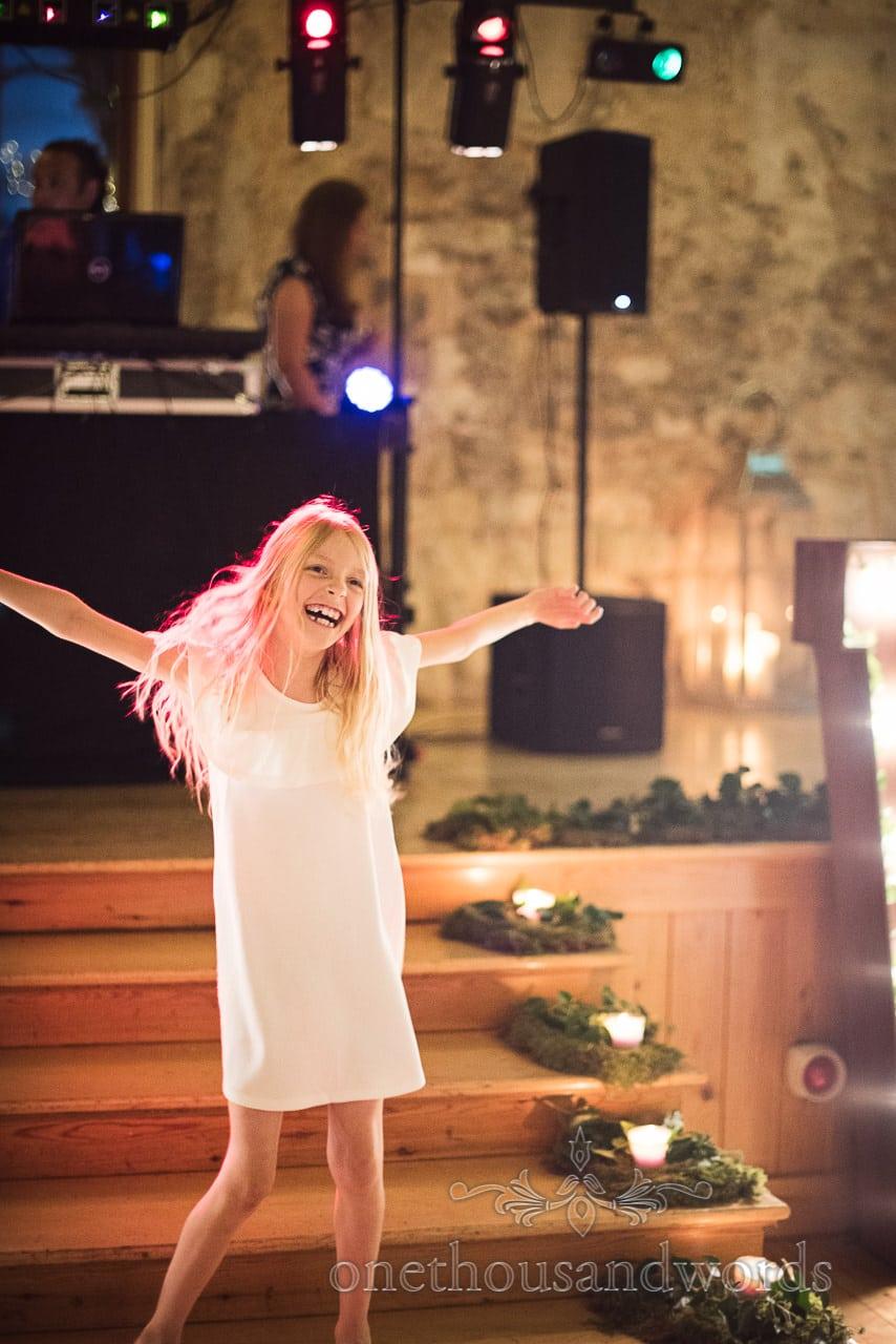 Child wedding guest dances with disco lights at Lulworth Castle Wedding