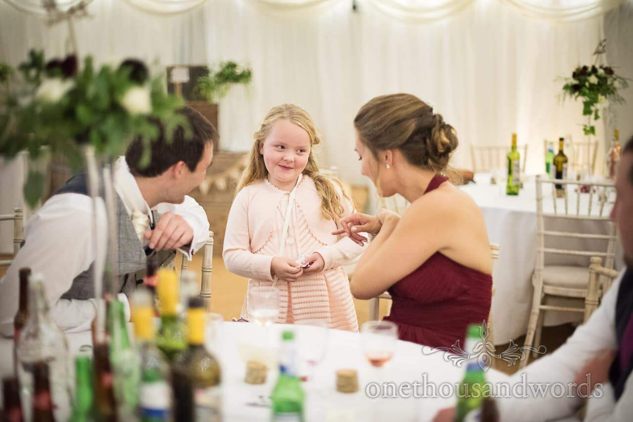 Child wedding guest talks to bridesmaid and grooms man in marquee