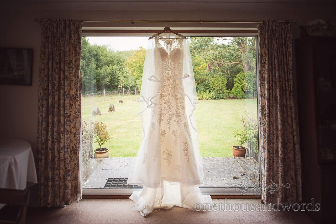 Classic wedding dress hangs in window on wedding morning